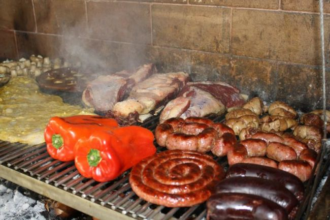 Visa to argentina for Asado grill packed with a variety of meats and vegetables.